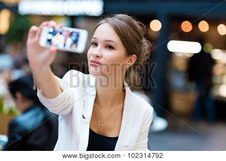Young, Beautiful Girl In A White Suit, Sitting In A Cafe And Shoots Self