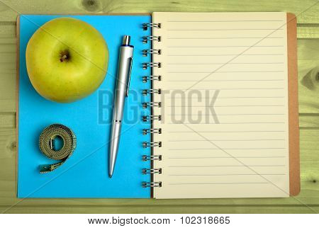 Notebook With Apple Fruit And Centimeter