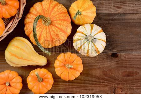 High angle shot of a Fall Gourd Still Life. Assorted gourds and pumpkins on a rustic dark wood background.