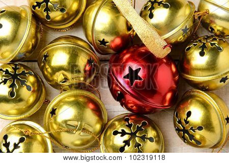 Closeup of a group of gold silver bells with one red one in the middle. The jingle bells fill the frame.