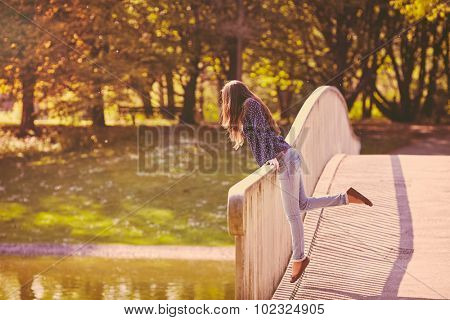 Retro colored full length portrait of young long-haired woman wearing blue shirt and jeans leaning on railing in summer park - lifestyle concept