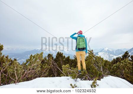 Back view of young woman wearing pink hat, blue jacket, green backpack, yellow pants and hiking boots standing against winter mountain valley looking far covering her eyes by hand - adventure concept