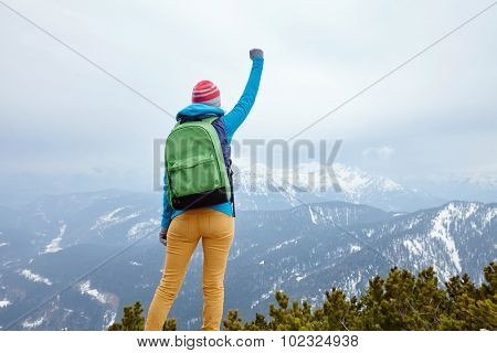 Back view of young woman wearing pink hat, blue jacket, green backpack and yellow pants raising her hand against winter mountains celebrating successful climb - goal concept