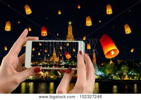 Back View Of A Woman Taking Photograph With A Smart Phone Camera At Wat Arun Under Loy Krathong Day