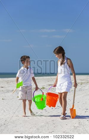 Happy children, boy girl, brother and sister having fun walking and playing in the sand on a beach with bucket and spade