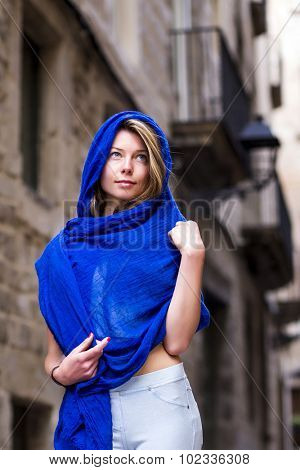 Woman covering herself with a blue veil, walking in the street