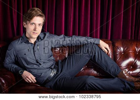 Man lounging on a couch in a club