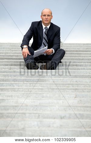 Portrait of businessman holding document on steps