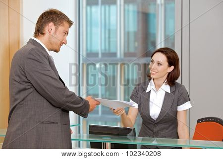 Young caucassian secretary assisting businessman