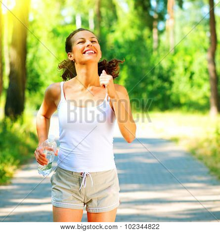 Woman running with bottle of water. Young sporty lady jogging outdoor in the park. Brunette model enjoy the training Workout. Exercises. Healthy lifestyle.