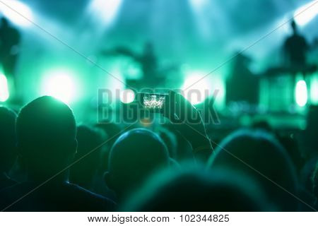 man in crowed with smart phone recording concert