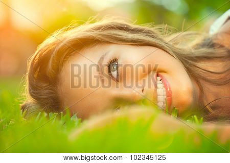 Beauty teenage Romantic Girl lying on the grass close-up. Outdoors. Brunette Model girl with blue eyes smiling and enjoying nature. Cute Teenage Girl lying on grass. Grassland. Sunshine