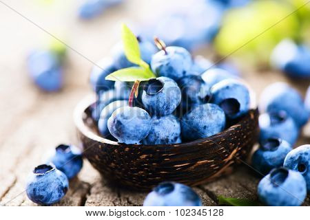 Blueberries in wooden bowl over rustic wooden table close up. Ripe and juicy fresh picked blueberry with green leaves. Berries harvest. Bilberries over wooden background. Berries. Diet concept
