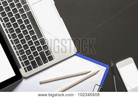 Overhead Of Black Board With Open Laptop, Mobilephone, Clipboard, And Stationery