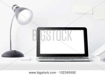 Laptop And Reading Lamp At Desk With Scrap Paper On The Wall