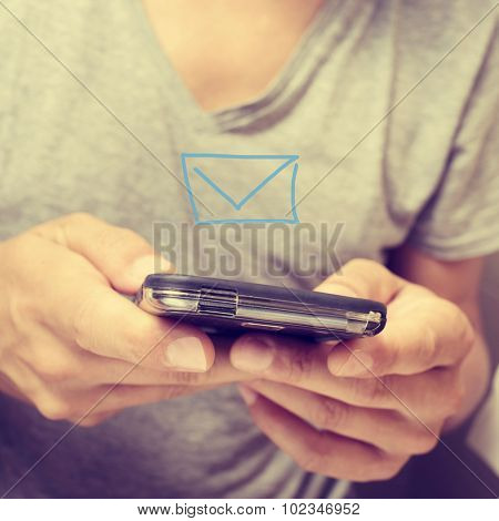 closeup of a young man in a sending a or receiving a text message with his smartphone
