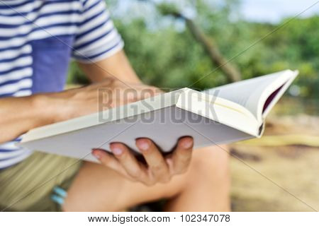 closeup of a young caucasian man reading a book outdoors in a natural landscape in a sunny day