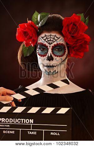 Filming woman in halloween santa muerte mask. Clapper board.