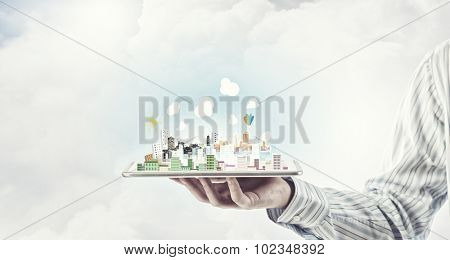 Hand holding tablet computer with cityscape on screen
