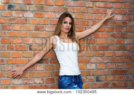 Young girl in a white t-shirt with outstretched arms posing next to a brick wall