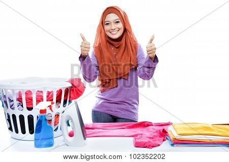 Young Woman Wearing Hijab Ironing Clothes And Giving Two Thumbs Up