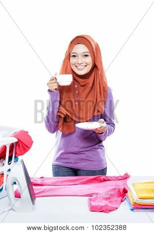 Young Woman Wearing Hijab Ironing Clothes While Enjoying A Cup Of Coffee