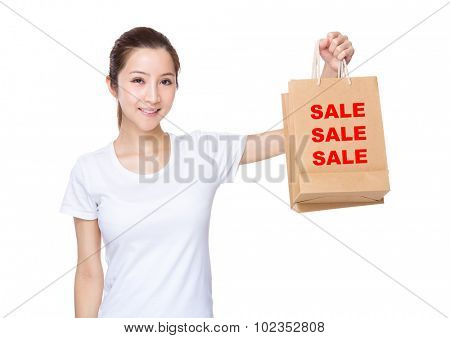 Woman carry with shopping bag and showing three words of sale