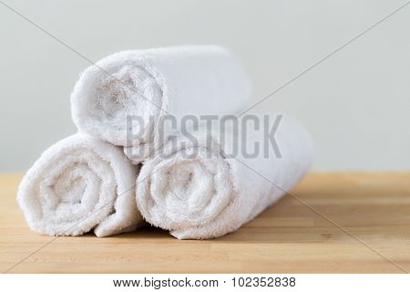 White spa towels pile on wooden table