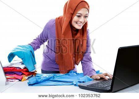 Multitasking Young Woman Wearing Hijab Watching Movie On Laptop While Doing Housework