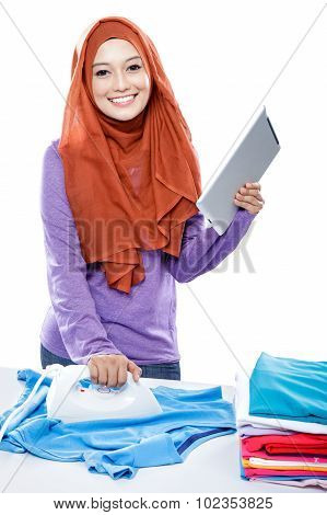 Young Woman Wearing Hijab Reading Article On Tablet While Ironing Clothes