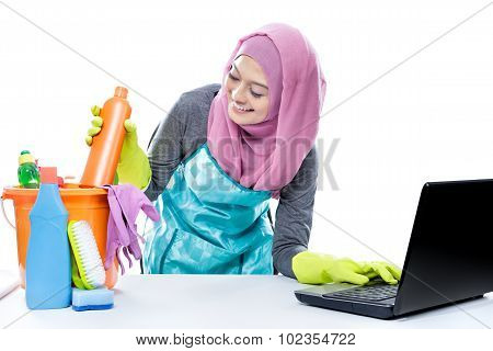 Multitasking Housewife Using Laptop While Pick Up A Bottle Of Cleaner