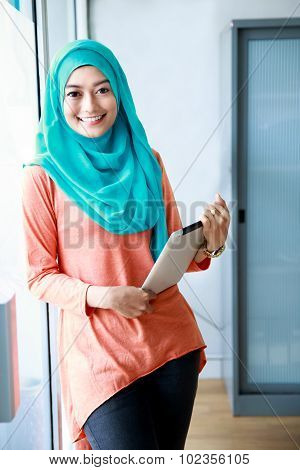 Beautiful Muslim Woman Smiling While Holding A Tablet