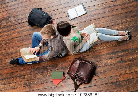 Girl and boy reading books leaning on each other on wooden floor having notebooks and bags around them.