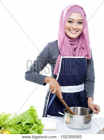 Young Woman Wearing Hijab Preparing Making Soup For Dinner
