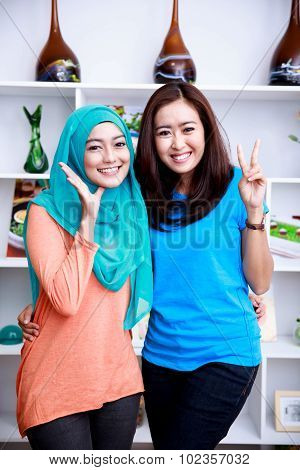 Two Friend Women Smiling And Posing At Living Room