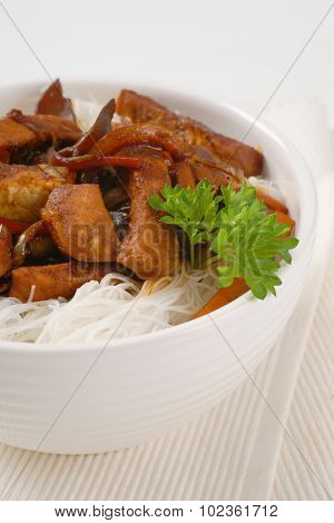 bowl of roasted meat, ear mushrooms and rice noodles on white place mat