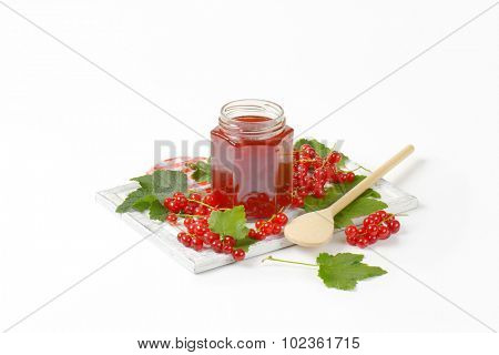 glass jar filled with red currant jam, standing on the wooden cutting board with kitchen cloth and wooden spoon, surrounded by fresh red currant clusters