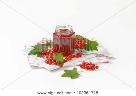 seasonal edition of red currant jam in the glass jar, on the kitchen cloth with spoon and clusters of fresh red currant with leaves