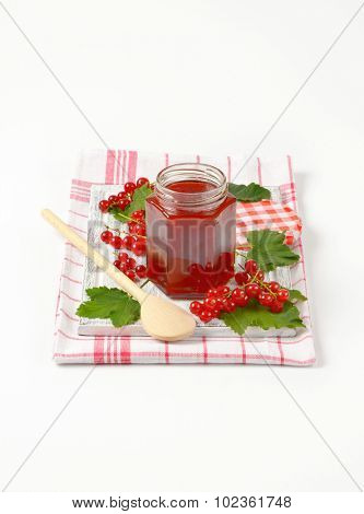 red currant jam preserved in the glass jar, on the kitchen cloth with wooden spoon and clusters of fresh red currant