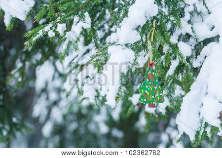 Handmade wooden ornament of fully decorated Christmas tree hanging on snowy spruce twig