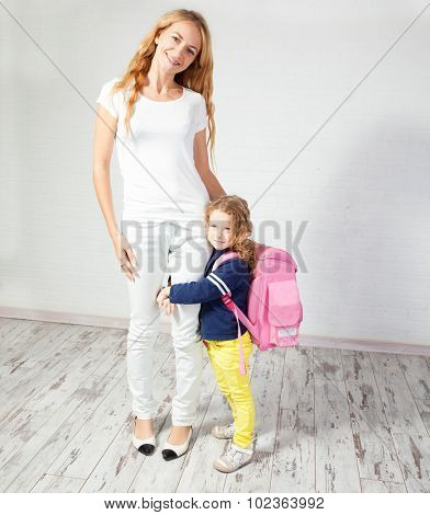 Mother helps her daughter get ready for school. Mom with child