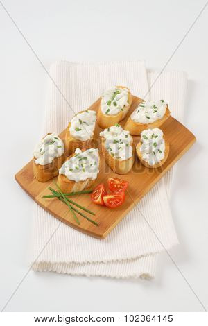 crunchy croutons with chives spread on wooden cutting board and white place mat