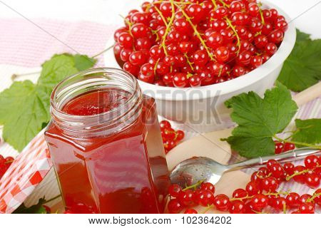 detail of glass jar filled with red currant jam, accompanied by a bowl with fresh red currant