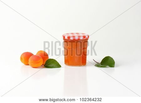 closed glass jar of apricot jam with three fresh apricots next