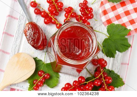 overhead detail of glass jar with red currant jam accompanied by tea spoon, wooden spoon and fresh red currant with leaves