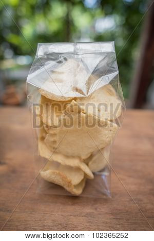 Thai crisp rice in transparent bag on the table.