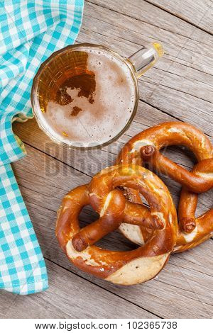 Beer mug and pretzel on wooden table. Top view