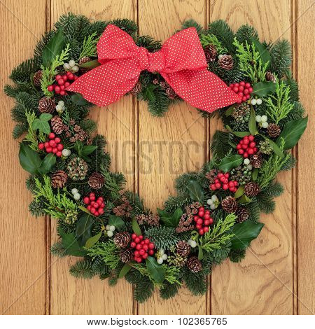 Christmas and winter heart shaped wreath with holly, mistletoe, red polka dot bow and greenery over oak background.