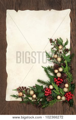 Christmas abstract background border with gold bauble decorations, holly, ivy, cedar cypress and fir on parchment paper over old oak wood.