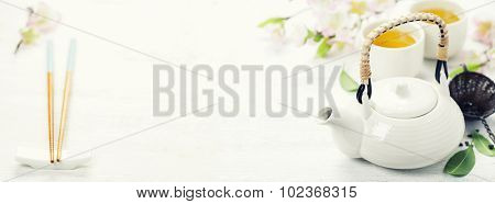 Chinese Tea Set  and sakura branch on bamboo mat